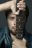 Big facial portrait of a guy with a guitar — Stock Photo
