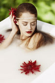Girl takes milk bath — Stock Photo