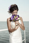 The beautiful bride smelling flowers — Stock Photo