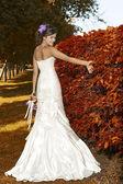 Portrait of a bride with a bouquet of autumn flowers — Stock Photo