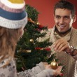 Stock Photo: Lovers decorate the Christmas tree