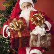 Boy dressed as Santa with gifts — Stockfoto