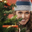 Beautiful girl looks out from behind fir — Stock Photo #32749527