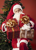Boy dressed as Santa with gifts — Stock Photo