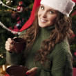 Stock Photo: Beautiful girl is drinking coffee on Christmas