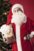 Boy dressed as Santa Claus with shopping — Stockfoto
