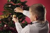 Boy dresses up Christmas tree — Stock Photo