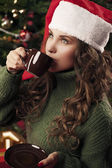 Beautiful girl is drinking coffee on Christmas — Stock Photo