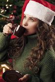 Beautiful girl is drinking coffee on Christmas — Stock Photo