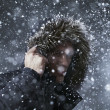 Adult male wearing jacket with fur hood in winter snow at night — Стоковая фотография