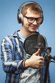 Close-up of a man recording vocals. Thumb up — Stock Photo