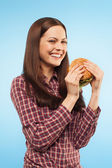 Girl eats a hamburger. Portrait in the studio. isolated — Stock Photo