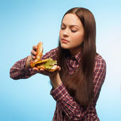 Girl prepares a burger. isolated — ストック写真