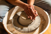 Hands working on pottery wheel , close up retro style — Stock Photo