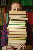The girl in library with a lot of books — Stock Photo