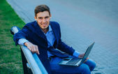 Happy business man using laptop outside on a park bench — Stock Photo