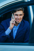 Smiling handsome businessman sitting in car. Young — Foto de Stock