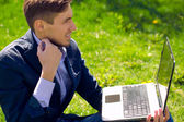 Young business man on the grass. fashion style. talking skype.  — Stock Photo