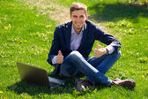 Young business man on the grass. fashion style. talking skype. o — Stock Photo
