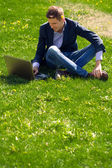 Young business man on the grass. talking skype. outdoor.  — Stock Photo
