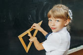 Portrait of smart schoolchild standing at blackboard and looking at camera — Stock Photo