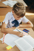 Little girl at the desk is writing — Stock Photo