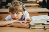 Smiling little student girl with many books at school — Stock Photo