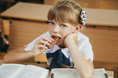 The girl is eating chocolate. School — Stock Photo