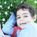 Smiling boy lying on grass — Stock Photo #24150195