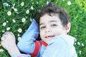 Usměvavý chlapec leží na trávě — Stock fotografie