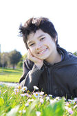 12 year old solar boy on the green grass — Stock Photo