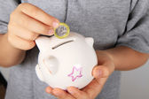 Child puts a euro in the piggy bank — Stock Photo
