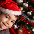 Happy child near the christmas tree — Stock Photo