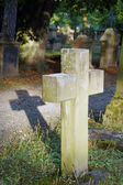 Ancient cemetery with a cross in the evening sun — Stock Photo