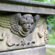 An angel head on an ancient grave stone — Stock Photo