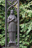 A grave stone with a weathered iron statue of Mary — Stock Photo