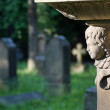 A beautiful angel's head smiles on the already dark cemetery — Stock Photo