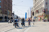 Amsterdam citycenter with three on their bike's — Stockfoto