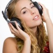 Christmas girl totaly in the mood and listening to christmas songs — Stock Photo