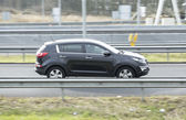 Kia Sportage driving down the road — Stock Photo