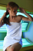 Beautiful girl sitting on a solarium — Stock Photo
