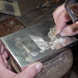 Silversmith affecting silver box - Stock Photo