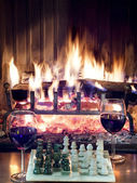 Play chess drinking red wine in front of roaring fireplace — Stock Photo