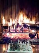 Grać w szachy, picie czerwonego wina przed kominkiem ryk — Zdjęcie stockowe