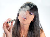 Brunette girl smoking electronic cigarette — Stock Photo
