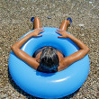 Foto de Stock  : Womsunbathing on shore of sein inflatable donut