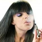 Beautiful girl smoking electronic cigarette — Stock Photo #31100793