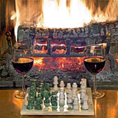Play chess drinking red wine in front of a roaring fireplace — Stock Photo