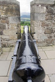 Cannon between battlements of castle — Stock Photo
