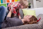 Mother and son playing on the couch — Stock Photo